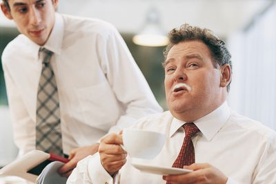 a manager with a milk mustache drinking a cappucino