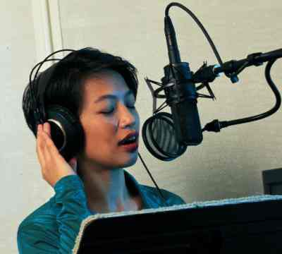 A photo of a woman singing into a microphone in a sound studio