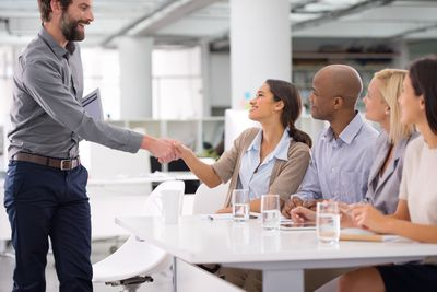 Man shaking hands at interview with four interviewers