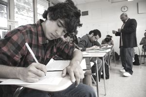 Close-Up of Student Writing in Classroom; Teacher and Students in Background