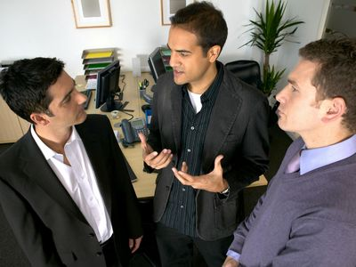 Three employees gossiping in the office