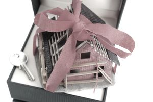 Gift box containing a miniature house and door key next to it.