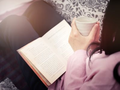 Midsection Of Woman Holding Coffee Cup And Book While Sitting On Sofa At Home