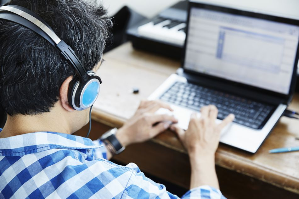 Man typing on laptop with headphones