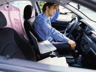 Weary man driving on a business trip with laptop and file folders on set next to him and button up shirt hanging in back seat