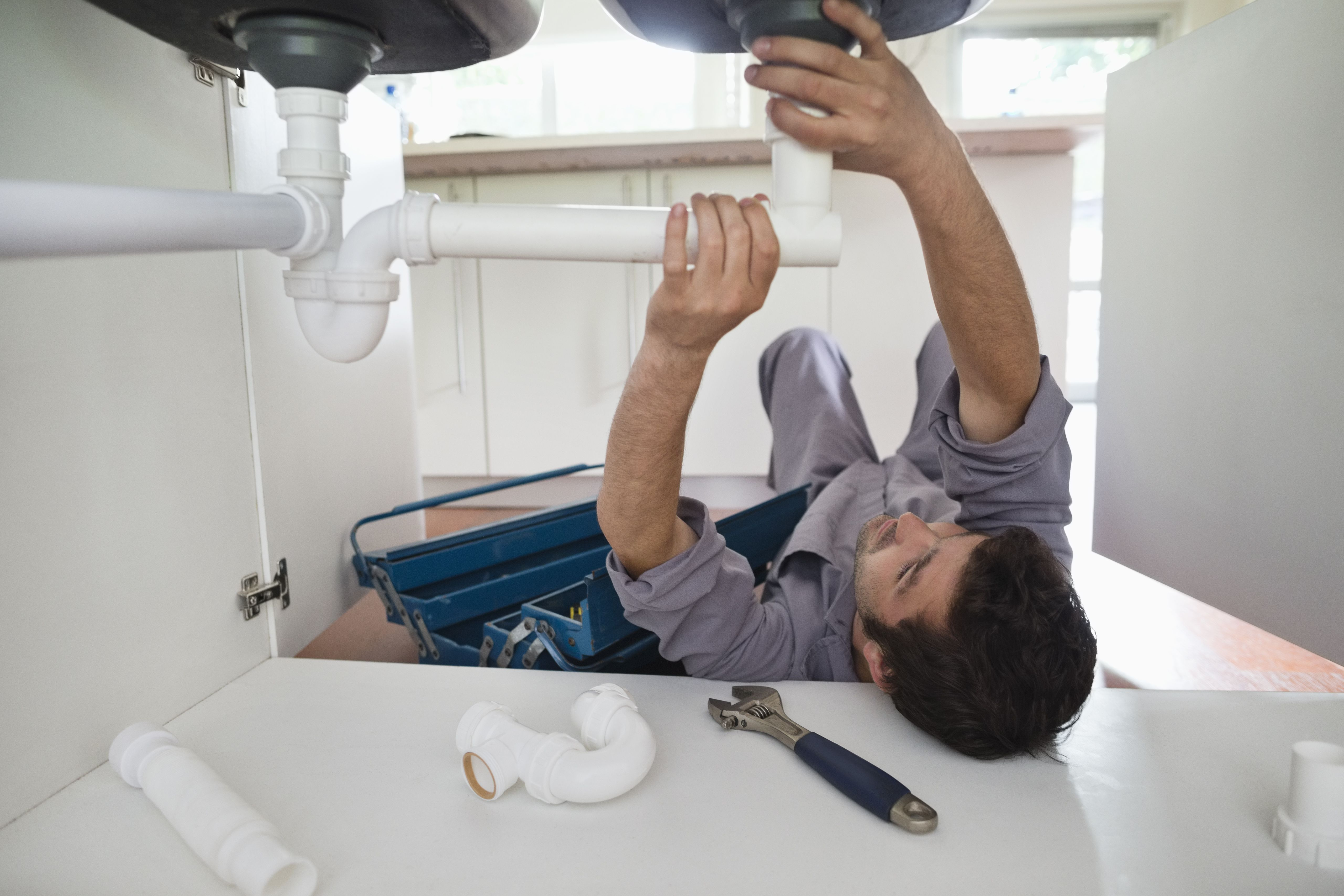 Plumber working on pipes under kitchen sink.