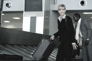 Traveling businesswoman picking up her suitcase at the airport luggage return.