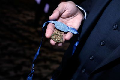 A hand holding the US medal of honor