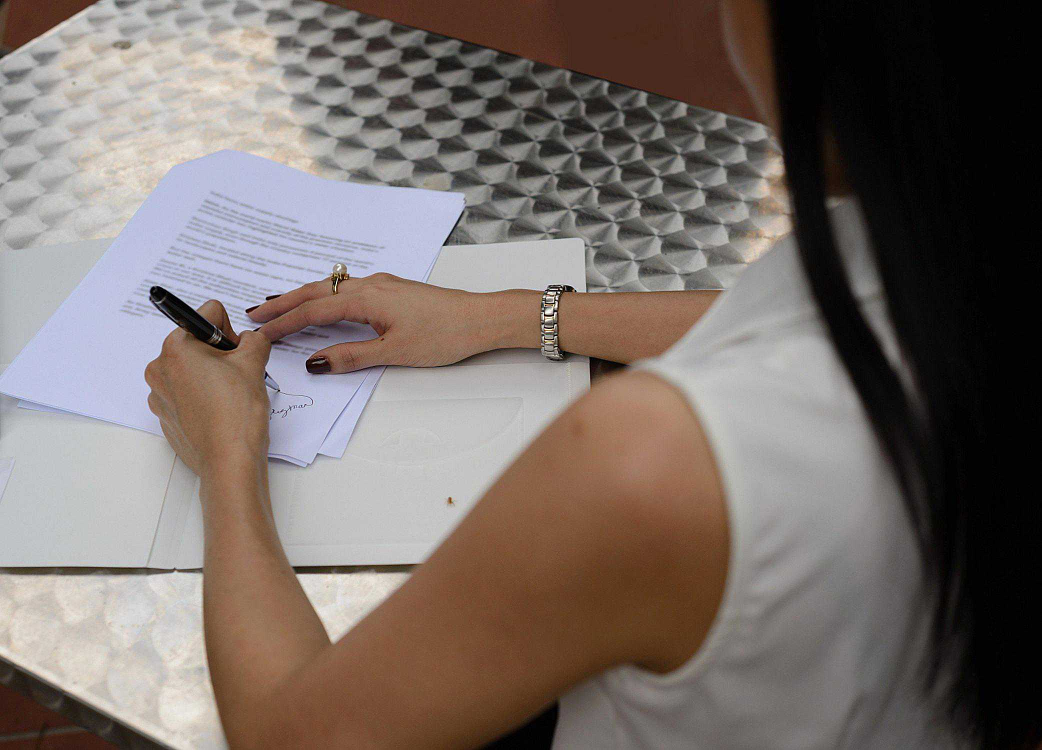 A picture of a woman signing a document