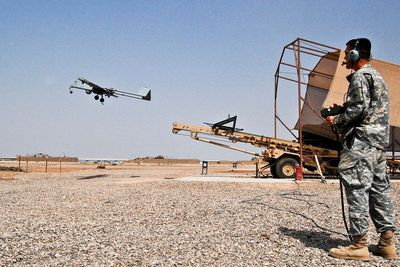 Soldier flying a Tactical Unmanned Aerial Vehicle over a field in Baghdad in 2008.