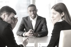 Black man interviewing facing skeptical HR managers