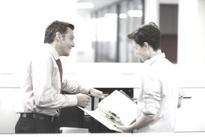 Businessman training a teenage intern in a office