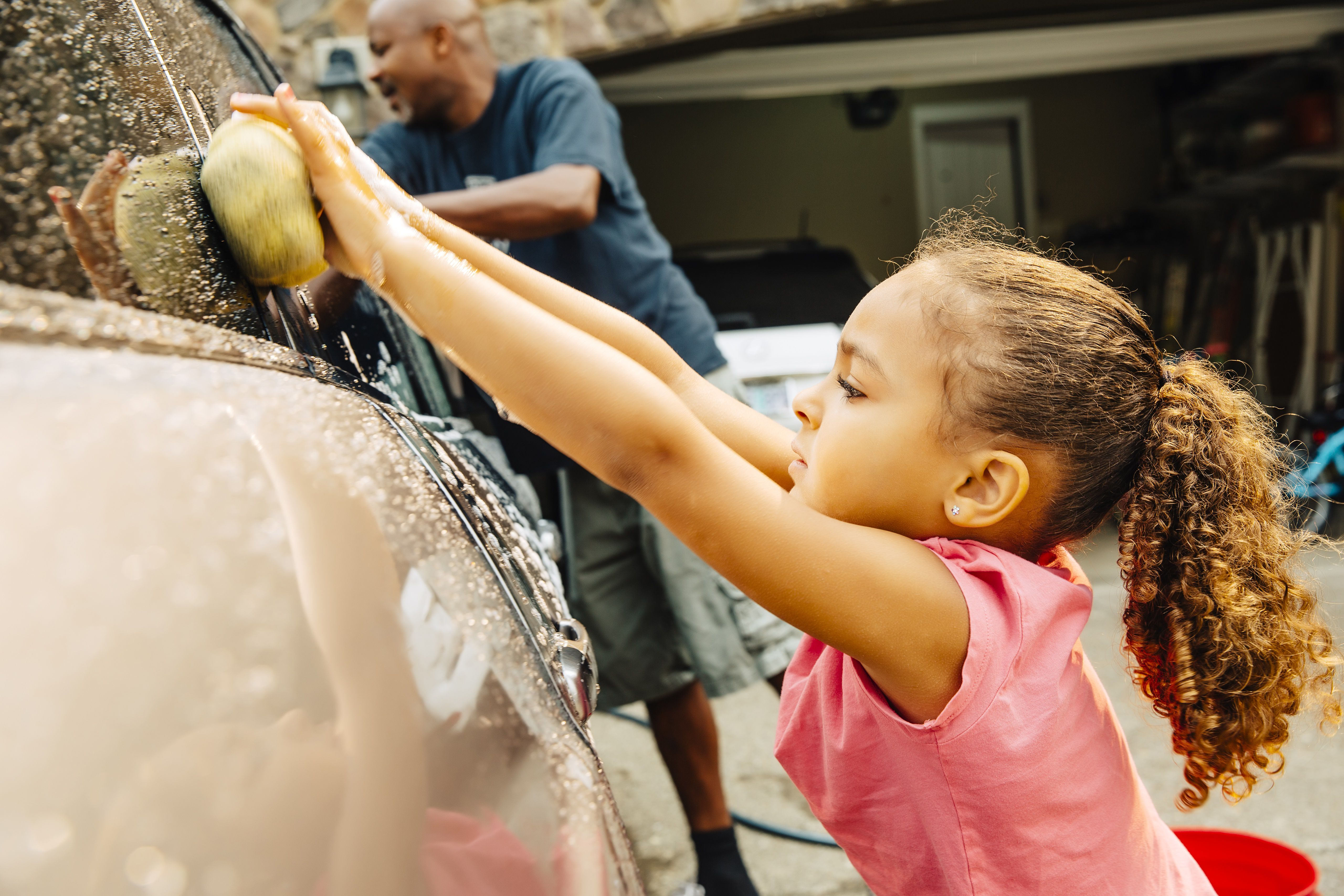 Father and daughter washing car