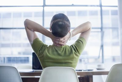 business woman rubbing her neck at her desk, frustrated with her job.