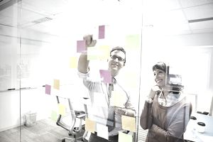 two people arranging sticky notes on wall
