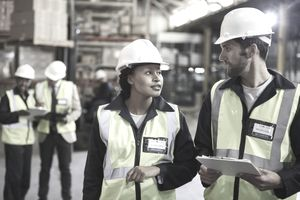 Workers with clipboard talking in distribution warehouse