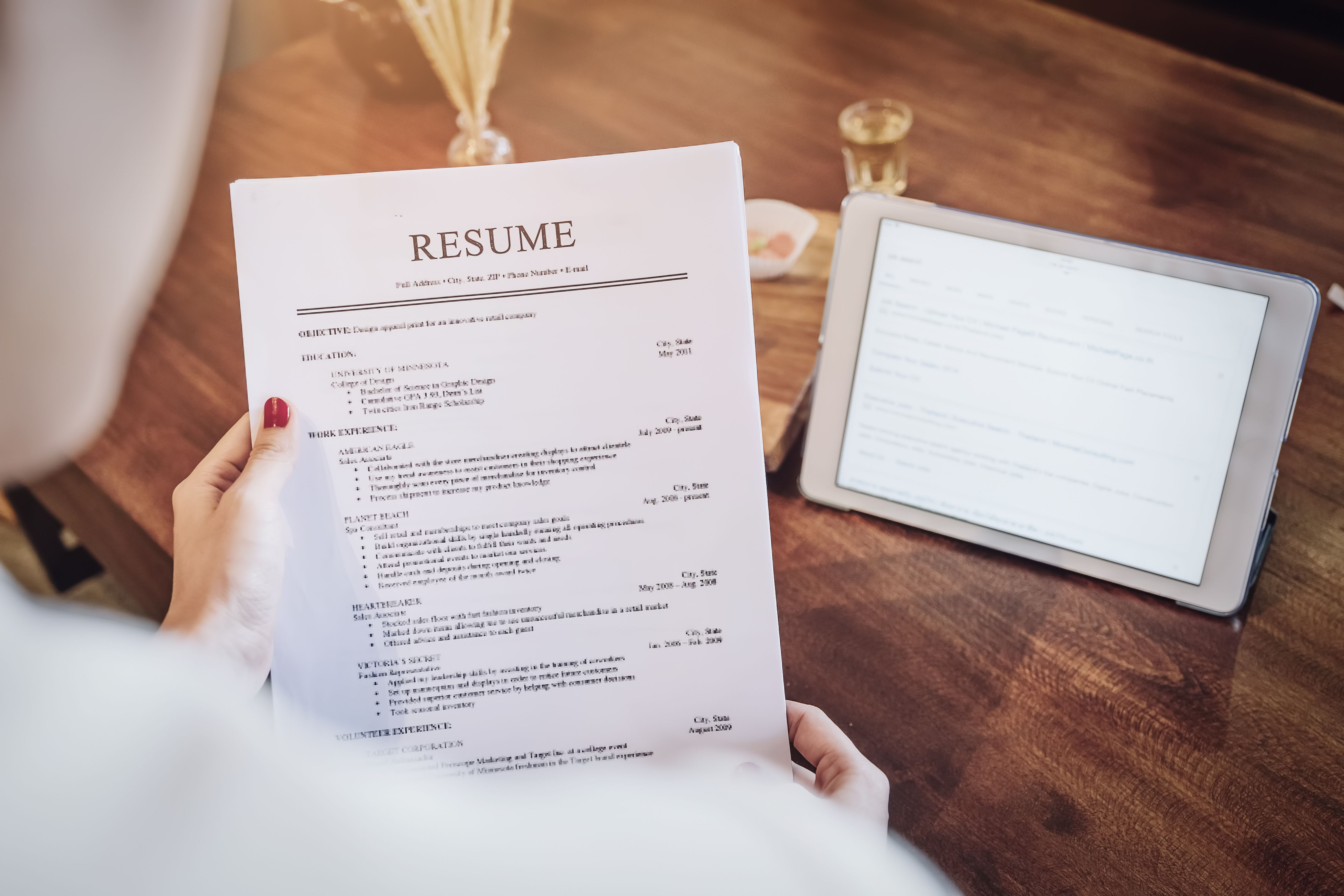 Person holding resume while searching for jobs online