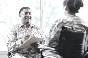 Army medical specialist talks with a patient in a wheelchair.
