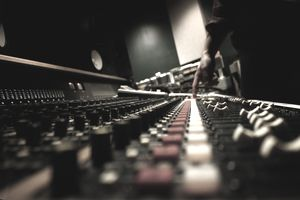 Closeup of a hand on a mixing board in a music studio