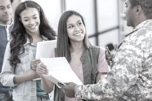 A group of young people talk with military recruitment officer