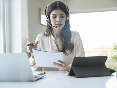 Woman wearing a headset working at home as a call center representative.