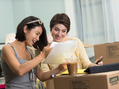 Two young women looking at paperwork for new apartment surrounded by moving boxes.