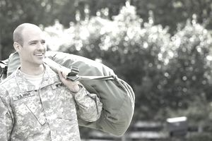 Caucasian soldier carrying duffel bag outdoors.