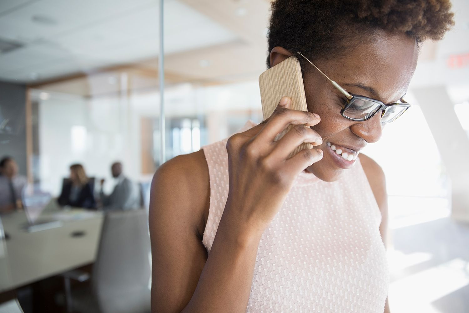 Smiling businesswoman talking on cell phone outside conference room meeting