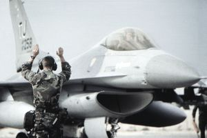 Air Force soldier guiding jet on a runway.