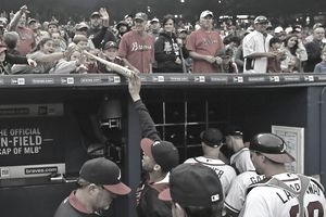 Braves fans reach for a bat from a player after the second baseball game in a double header against the St. Louis Cardinals at Turner Field on October 4, 2015, in Atlanta, Georgia.
