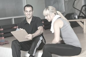 Male personal trainer talking to female client