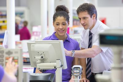 Supermarket manager training young cashier how to use checkout register