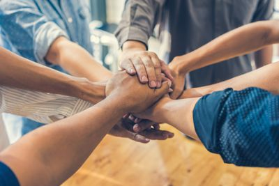 Circle of employees placing hands on top of each others hands depicting team trust
