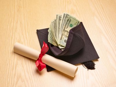 Diploma next to a graduation cap with money inside