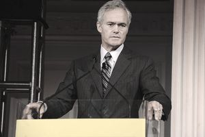 Scott Pelley standing on stage giving a talk