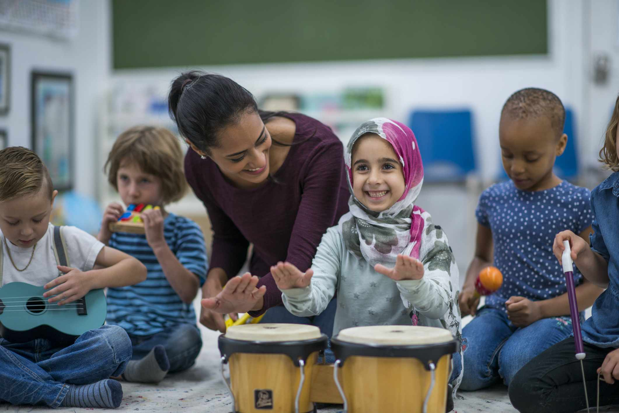 Little girl beating congas with music instructor in class at school with her friends