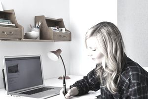 Blonde girl studying at desk with laptop