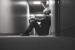 Man sitting on floor in corridor looking blindsided after receiving news about being laid off
