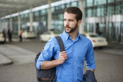 Young businessman with backpack on the go