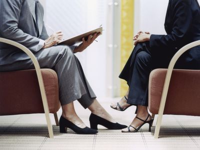Two women sitting opposite each other while one is interviewing for a job.