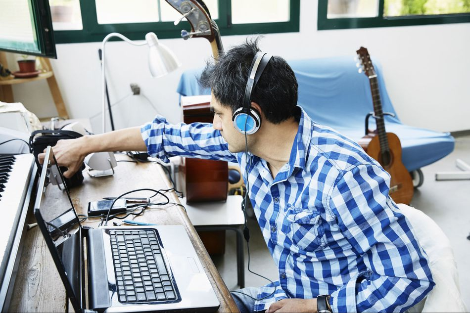 Mature male composer connecting laptop to keyboard instrument in music studio
