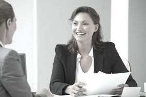 Woman at desk with papers smiling at woman across from her