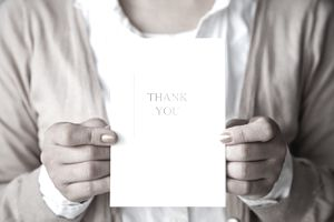 a woman holding a card with a message, THANK YOU, written on it.