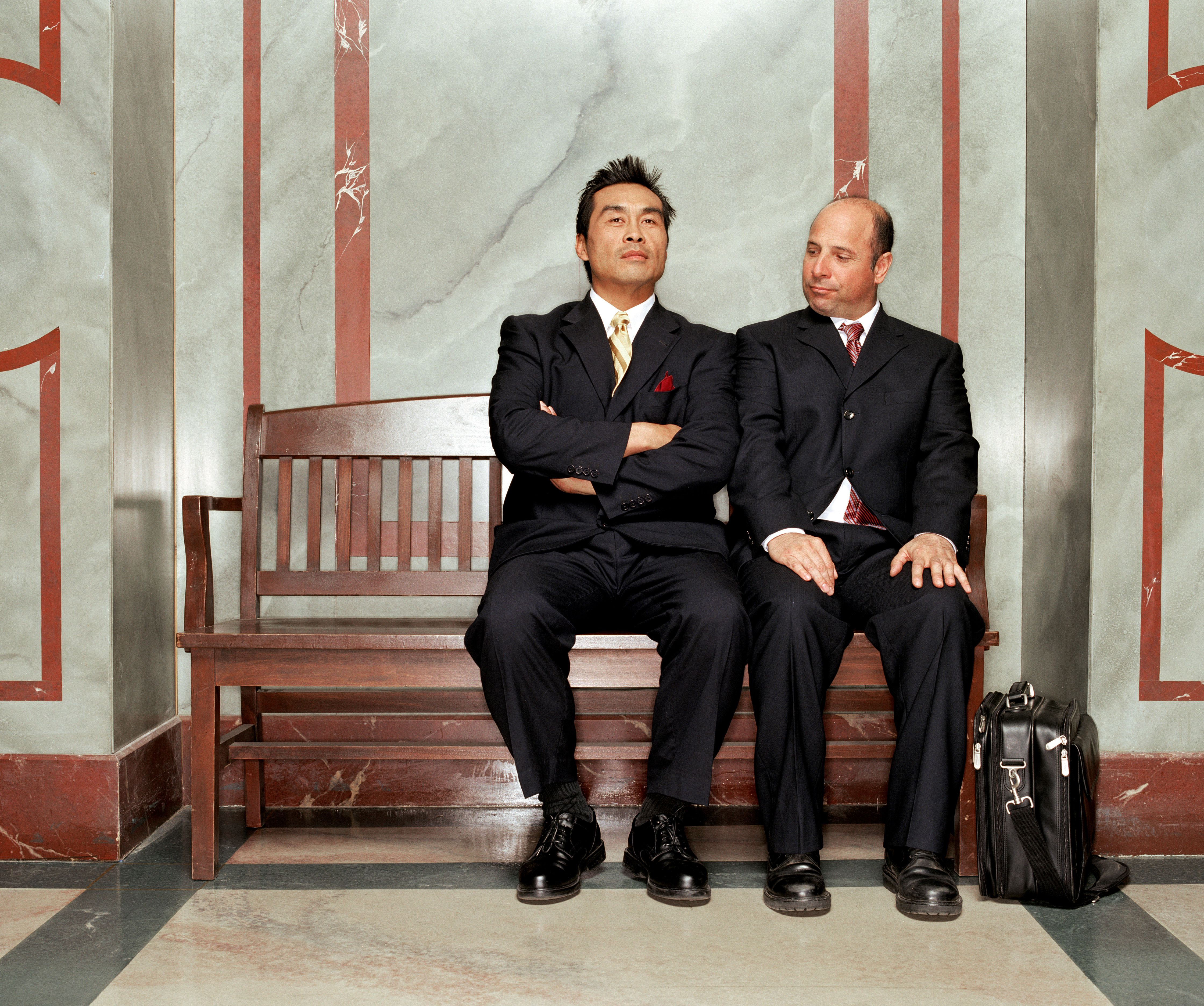 Two mature businessmen sitting on bench