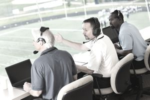 Professional sports commentators in press box at football game
