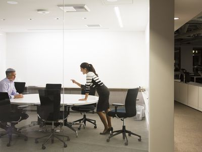 female superior scolding a male coworker in a conference room