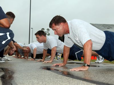 Air Force service members doing push ups as part of a fitness assessment test.