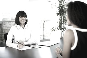 Businesswoman at office desk conducting an interview with a prospective salesperson.