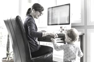 A mother is working from home while looking after her child.