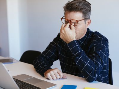 Businessman at desk in office rubbing his eyes, frustrated with his job.
